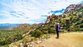 Senior woman hiker enjoying the view of the Valley of the Sun and the McDowell Mountain Range viewed from the Tom`s Thumb Trail. Senior woman hiker enjoying the royalty free stock photography