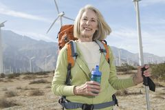 Senior Woman With Hiking Pole And Backpack At Windfarm Royalty Free Stock Image