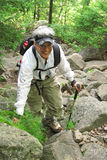Senior Woman hiking on rocks. Senior woman hiking mountain trail over rocks with backpack and walking stick Stock Images