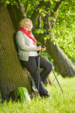 Senior woman with hiking sticks on a tree Royalty Free Stock Photography