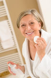 Senior woman hold cotton pad make-up removal stock images