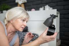 Senior woman holding alarm clock checking out time. Portrait of senior woman holding alarm clock checking out time stock photos