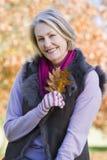 Senior woman holding autumn leaf outdoors Royalty Free Stock Image
