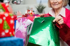 Senior Woman Holding Bags During Christmas. Midsection of senior woman holding bags during Christmas at home Stock Image