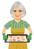 Senior woman holding baking tray with heart shape cookies stock illustration