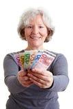 Senior woman holding banknotes. Happy senior woman holding many Euro banknotes Royalty Free Stock Images