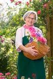 Senior woman holding basket full of flowers Stock Photography