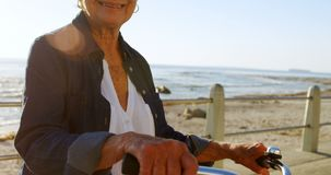 Senior woman holding bicycle at promenade 4k stock video footage