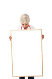 Senior woman holding blank poster stock photography