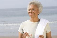Senior Woman Holding Bottle And Towel At Beach Royalty Free Stock Image