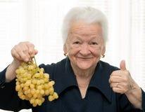 Senior woman holding a bunch of grape Stock Photos
