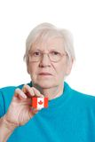 Senior woman holding canada day flag sticker focus Royalty Free Stock Photo