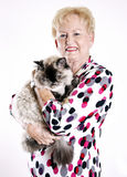 Senior woman holding cat. A smiling senior woman holding her cat royalty free stock photos