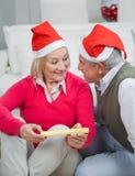 Senior Woman Holding Christmas Gift Looking At Man Royalty Free Stock Photo