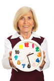 Senior woman holding clock Stock Images