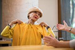 Senior woman holding clothes. Stock Photo