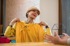Senior woman is holding clothes. Royalty Free Stock Image