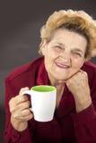 Senior woman holding a cup Stock Photos
