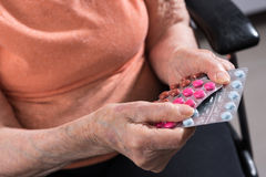 Senior woman holding different medication package Stock Image