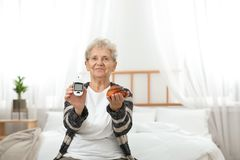 Senior woman holding digital glucometer and pastry. Diabetes diet royalty free stock photos