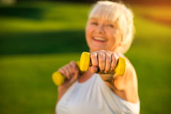 Senior woman holding dumbbell. Elderly lady with smiling face. I train to become healthier. Fight with the laziness Stock Images