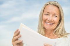 Senior Woman Holding Envelopes Against Sky Stock Photo