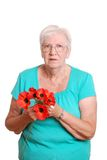 Senior woman holding fake red poppies Royalty Free Stock Photo