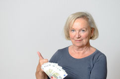 Senior Woman Holding Fan of Euros with Thumbs Up Stock Photography