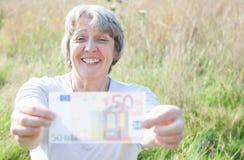 Senior woman holding fifty euro Royalty Free Stock Photo