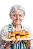 Senior woman holding fresh buns over white Stock Photography