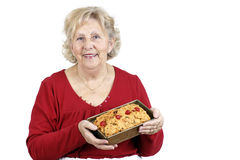 Senior woman holding a fruit cake Royalty Free Stock Photos