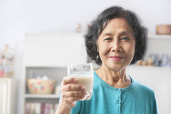 Senior woman holding glass of milk. Offerng to camera. PS: shallow depth of field Royalty Free Stock Image