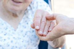 Senior woman holding hands with caretaker Royalty Free Stock Photos