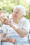 Senior Woman Holding Hands with Caretaker. Happy senior woman holding hands with her caretaker stock photo