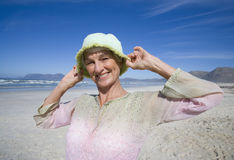 Senior woman holding hat on head on beach, smiling, portrait, close-up Royalty Free Stock Image