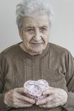 Senior woman holding heart shaped gift Stock Photo