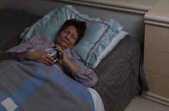 Senior woman holding her alarm during sleepless night while in b royalty free stock photos