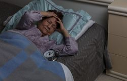 Senior woman with headache during nighttime while in bed stock images
