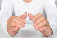 Senior woman holding her hands protectively above table Stock Photography