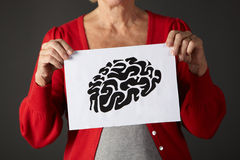 Senior woman holding ink drawing of brain Royalty Free Stock Photo