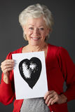 Senior woman holding ink drawing of heart. Depicting her good health Royalty Free Stock Photos