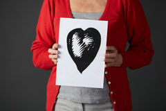 Senior woman holding ink drawing of heart Stock Image