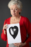 Senior woman holding ink drawing of heart. Looking very worried Stock Photography