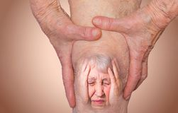 Senior woman holding the knee with pain. Collage. Concept of abstract pain and despair. The elderly pensioner and her problems. Old age and illnesses. 86-year stock photo