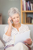 Senior woman holding mobile phone while looking documents Royalty Free Stock Images