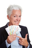 Senior woman holding money fan Stock Photography