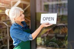 Senior woman holding open sign in organic produce shop stock images