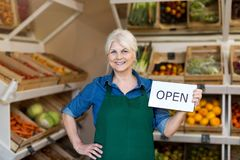 Senior woman holding open sign in organic produce shop royalty free stock images