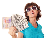 Senior woman holding passport and money. Royalty Free Stock Image