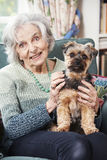 Senior Woman Holding Pet Dog Indoors Stock Image